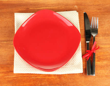Empty square red plate with fork and knife on wooden table, close-up Stock Photo - 16895322
