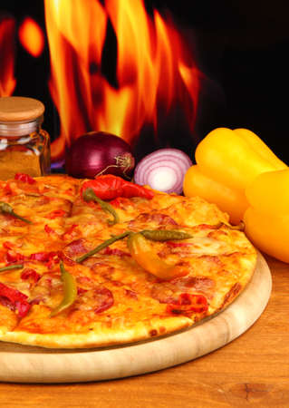 Tasty pepperoni pizza with vegetables on wooden board on flame background photo
