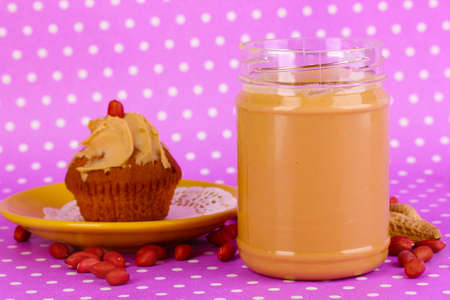 Delicious peanut butter with cake on purple background with polka dots photo