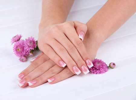 Woman hands with french manicure and flowers on white wooden background photo