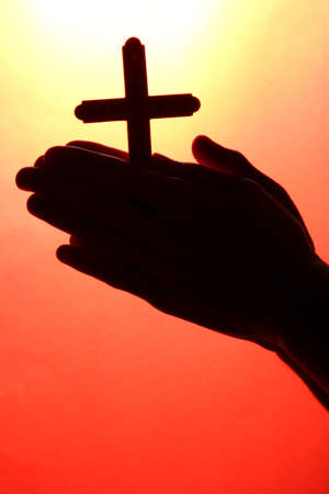 man hands with crucifix, on red background  photo