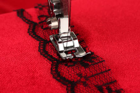 needle lace: Closeup of sewing machine working part with  red cloth