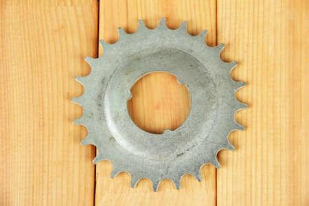 Metal cogwheel on wooden background photo