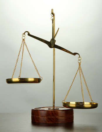 Gold scales of justice on grey background photo