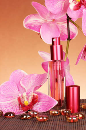 Womens perfume in beautiful bottle with orchids on brown background photo