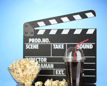 Movie clapperboard, cola and popcorn on blue background Stock Photo - 16911159