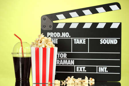 Movie clapperboard, cola and popcorn on background photo