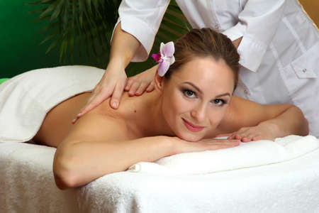 beautiful young woman in spa salon getting massage, on green background Stock Photo - 17282397