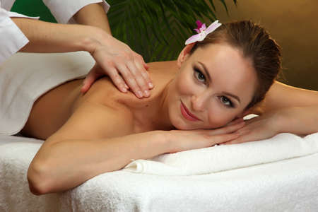 beautiful young woman in spa salon getting massage, on green background Stock Photo - 17282459