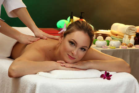 beautiful woman in spa salon with stones getting massage, on green background photo