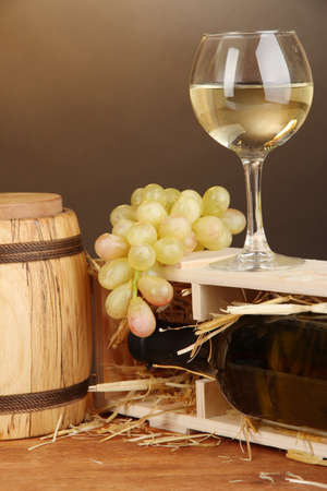 Wooden case with wine bottle, barrel, wineglass and grape on wooden table on brown background Stock Photo - 16912364