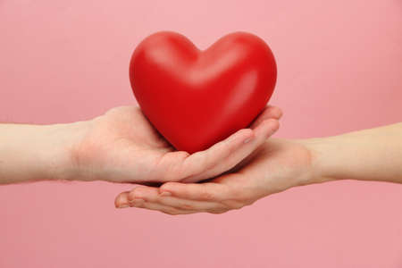 Red heart in woman and man hands, on pink background photo