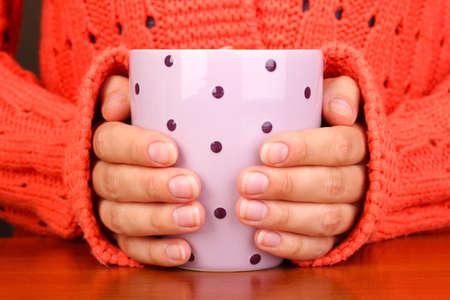 warm colors: manos que sostienen la taza de bebida caliente de cerca