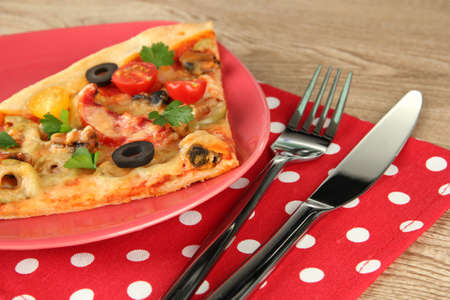 plate with a slice of delicious pizza on wooden background Stock Photo - 16940015