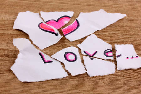 Torn paper with words Love close-up on wooden table photo