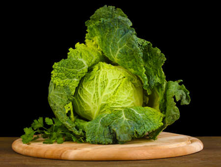 Fresh savoy cabbage on wooden table on black background photo