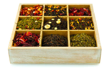 assortment of dry tea in wooden box, isolated on white photo