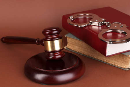Gavel, handcuffs and book on law on brown background Stock Photo - 16939347