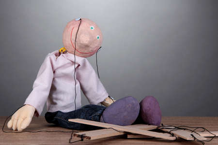 1 person: Wooden puppet sitting on grey background
