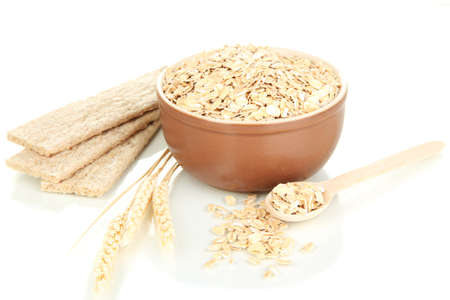 Brown bowl full of oat flakes with spikelets, oat biscuits and wooden spoon isolated on white Stock Photo - 16939043