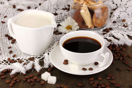 A cup of strong coffee and sweet cream on wooden table close-up photo