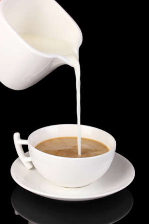 Delicate cream poured into cup of coffee isolated on black Stock Photo - 16937867