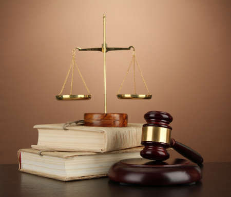 business law: Golden scales of justice, gavel and books on brown background Stock Photo