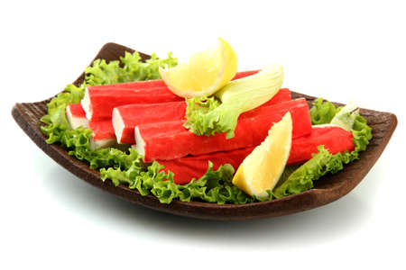 Crab sticks with lettuce leaves and lemon on plate isolated on white Stock Photo - 16939066