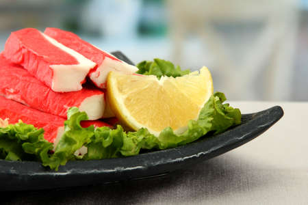 Crab sticks with lettuce leaves and lemon on plate, close up photo