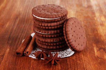 Chocolate cookies with creamy layer on wooden table close-up photo