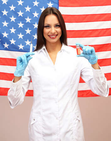 Portrait of female doctor or scientist with syringe on  background of American Flag photo