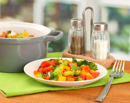 paprica: Vegetable stew in gray pot on wooden table on bright background