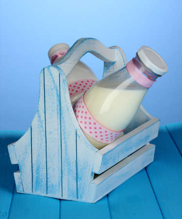 Milk in bottles in wooden box on blue wooden table on blue background photo