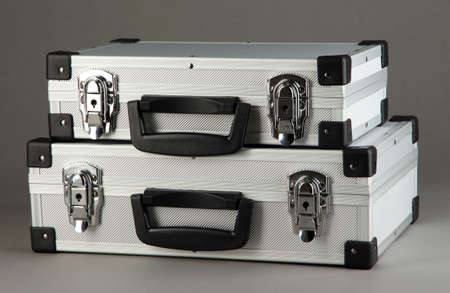 Silvery suitcases on grey background photo