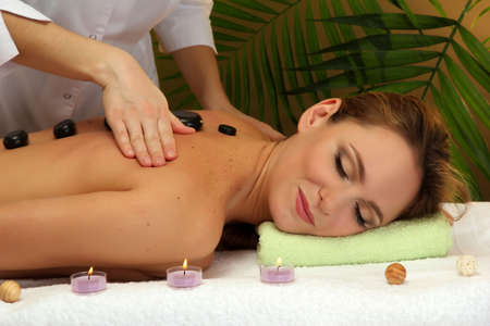 beautiful young woman in spa salon getting massage with spa stones, on green background photo