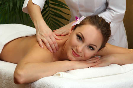 beautiful young woman in spa salon getting massage, on green background Stock Photo - 17282405