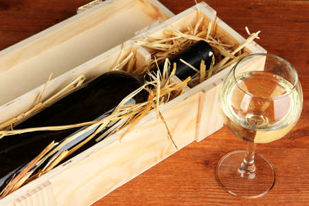 Wooden case with wine bottle on table photo