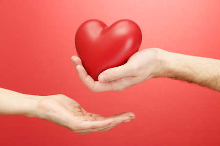 Red heart in woman and man hands, on red background Stock Photo - 16939277