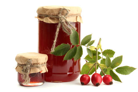 jars with hip roses jam and ripe berries, isolated on white photo