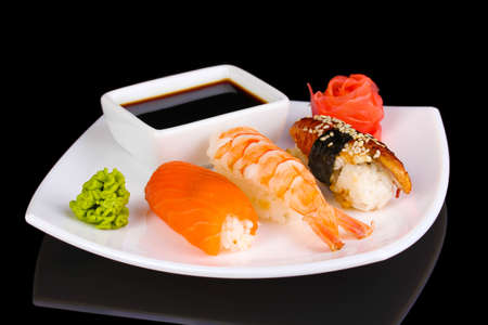 delicious sushi served on plate isolated on black photo