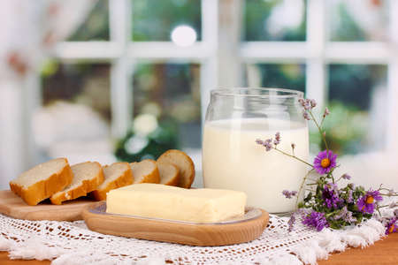 Butter on wooden holder surrounded by bread and milk on window background photo