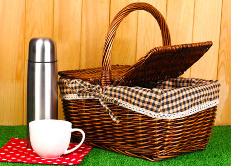 metal thermos with cup and basket on grass on wooden background photo