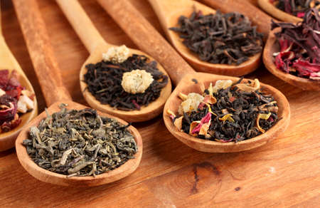 assortment of dry tea in spoons, on wooden background Stock Photo - 16965621