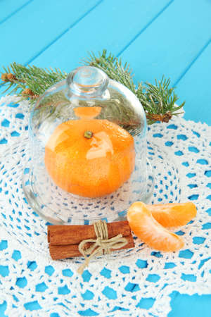 Tangerine on saucer under glass cover on blue background photo