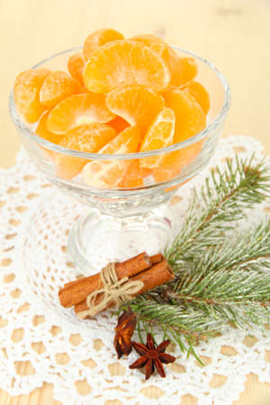 Tasty mandarine's slices in glass bowl on light background photo