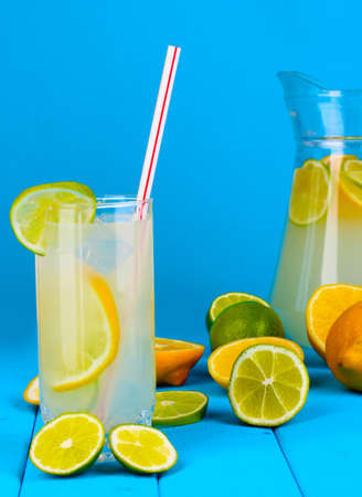 Citrus lemonade in pitcher and glass of citrus around on wooden table on blue background photo