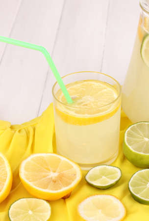 Citrus lemonade in glass and pitcher of citrus around on yellow fabric on white wooden table close-up photo