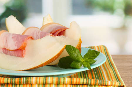 parma ham and melon, on wooden table photo