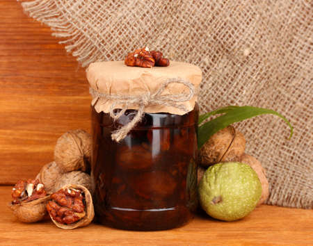 jam-jar of walnuts on a wooden background photo