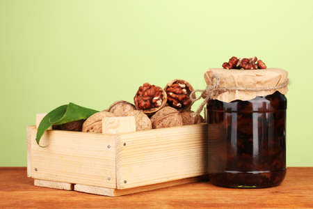 jam-jar of walnuts and  wooden box on green  background photo